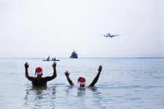 Two men in Santa Claus red hat greet salute airplane in morning. Hangover after Christmas holiday party Stock Images