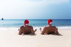 Two men in Santa Claus red hat sit on the beach in morning hango. Ver Christmas holiday party dreams Royalty Free Stock Photo