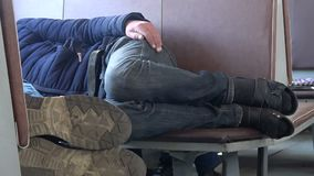 Two men of a scruffy look sleep on the seats in a passenger train. Two men of a slovenly appearance sleep lying on the seats in a moving passenger train stock video