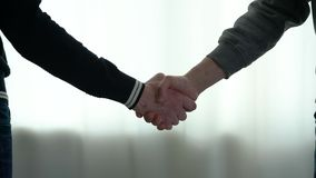Two men shake hands. Close-up stock video footage