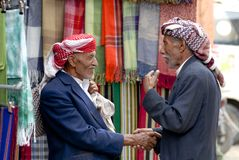 Two men shake hands at the market in Sana'a, Yemen. Royalty Free Stock Photos