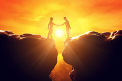 Two men shake hands over precipice. Business deal. Two men shake hands over precipice between two rocky mountains at sunset. Business, deal, handshake Stock Image
