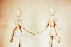 Two men shake hands to each other. Abstract image with wooden puppets Royalty Free Stock Images