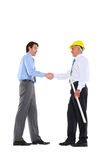 Two men shaking hands. Architect with helmet and plan Royalty Free Stock Photo