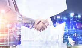 Two men shaking hands and a city Stock Photos