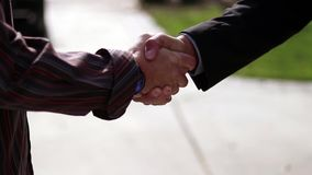 Two men shaking hands. Close-up video capture of two men shaking hands over a successful business deal stock video