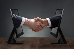 Two Men Shaking Hands Coming Out From Computer. Close-up Of Two Men Shaking Hands Coming Out From Computer Against The Gray Background Royalty Free Stock Photos