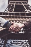 Two Men Shaking Hands By The Eiffel Tower. In Paris Stock Photography