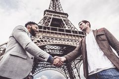Two Men Shaking Hands By The Eiffel Tower. In Paris Royalty Free Stock Image