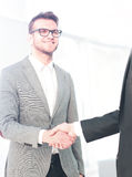 Two men shaking hands and looking at each other with smile Royalty Free Stock Photo