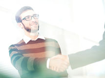 Two men shaking hands and looking at each other with smile Stock Image