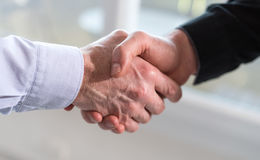 Two men shaking hands in office. Two businessmen shaking hands in office Stock Photos