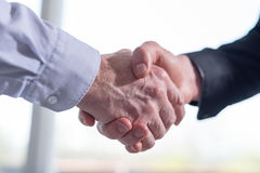 Two men shaking hands in office. Two businessmen shaking hands in office Royalty Free Stock Photo