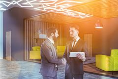 Two men shaking hands in office lounge area stock photography