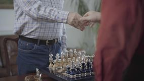 Two men shaking hands over a chess board before start game and sit at the small table. The beautiful chess set with. Two men shaking hands over a chess board stock footage
