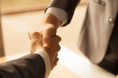 Two men shaking hands over sunny office background. Partnership. Businessmen shake hands.Two men shaking hands over sunny office background stock photography