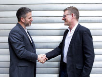 Two men shaking hands. Two men in suits are shaking hands and smiling Royalty Free Stock Image