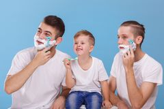 Two men shave their beard and little boy cleans teeth with. On a blue background. Two European young men shave their beard with foam and a razor and a little Stock Photo