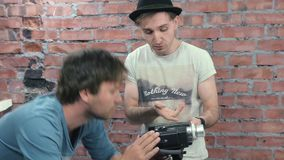 Two men shoot someone on camera. Discussion. Dispute. Brick wall on background. Two men shoot someone on camera. Discussion. Deliberation. Dispute. Brick wall on stock footage