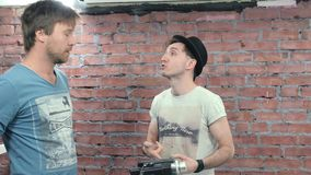 Two men shoot someone on camera. Dispute. Wrangle. Brick wall on background. Two men shoot someone on camera. Discussion. Wrangle. Dispute. Brick wall on stock video