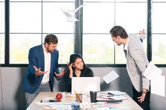 Two men shout the girl and scatter documents, the girl works for the laptop. Inside the office. royalty free stock photos