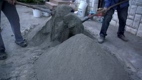 Two men shovel lime and sand stock video footage
