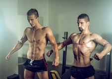 Two men showing body in gym Royalty Free Stock Photos