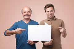 Two men showing empty copyspace for ad. stock images