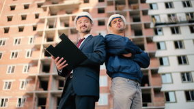 Two men are showing a thumb near the construction. Two foremen are standing near the construction. The men are smiling and showing thumb stock video