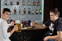 Two men showing thumbs up while drinking beer. Two Caucasian happy young men showing thumbs up while sitting at the bar drinking beer royalty free stock images