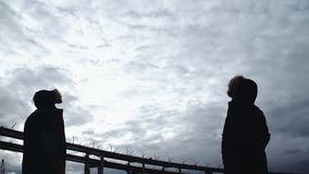 Two men silhouettes standing on river shore with highway bridge. Two men silhouettes in winter jackets standing on river shore with highway bridge on background stock video footage