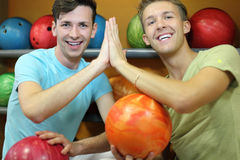 Two men sit near shelves in bowling club. Two happy men sit near shelves with balls, touch hands and look at camera in bowling club; shallow depth of field Stock Image