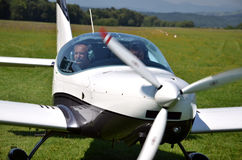 Two men sit into ultralight propeller-driven airplane and get ready for taking off. Ocova, Slovakia - August 2, 2014: Two men sit into ultralight propeller Royalty Free Stock Photos