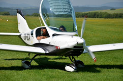 Two men sit into ultralight propeller-driven airplane and get ready for taking off Stock Photo