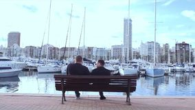 Two men sitting on bench near the yacht parking. Stock. Men sitting on bench overlooking sea. Two businessmen sit on the. Two men sitting on bench near the yacht stock video footage