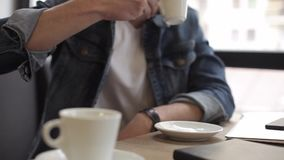 Two men sitting in cafe drinking coffee. Two handsome men sitting in cafe and chatting with each other. Young attractive guy in jeans jacket drinking a cup of stock video footage