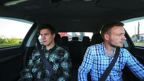 Two men sitting in the car, driving, looking aside. In full HD stock video footage