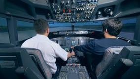 Two men are sitting in a cockpit of a flight simulator. Cockpit cabin flight deck.