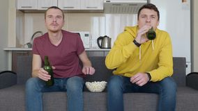 Two men sitting on the couch watch a football match on TV, drink beer and eat popcorn stock video footage