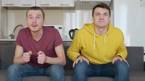 Two men sitting on the couch watch a football match on TV and enjoy the victory of their favorite team. One of the guys gets up off the sofa and waves his arms stock video footage