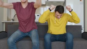 Two men sitting on the couch watch a football match on TV and enjoy the victory of their favorite team. One of the guys gets up from the sofa and claps his stock footage