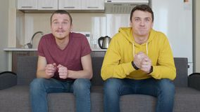 Two men sitting on the couch watch a football match on TV and enjoy the victory of their favorite team. Young guys are in favor of sports game and shout for stock video footage