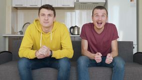 Two men sitting on the couch watch a football match on TV and enjoy the victory of their favorite team. Young guys get up from the sofa and hug each other for stock footage