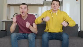 Two men sitting on the couch watch a football match on TV and enjoy the victory of their favorite team. Young guys get up from the sofa and hug each other for stock video footage