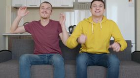 Two men sitting on the couch watch a football match on TV and enjoy the victory of their favorite team. Young guys laugh and give five to each other. The stock footage