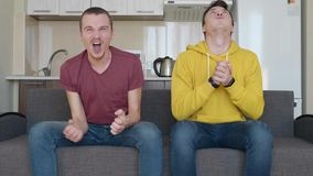 Two men sitting on the couch watch a football match on TV and enjoy the victory of their favorite team. Young guys laugh and shout for joy. The kitchen on the stock video footage