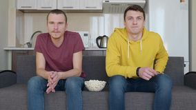 Two men sitting on the couch watch a football match on TV with popcorn bowl stock video