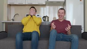 Two men sitting on the couch watch a football match on TV and support different teams