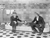Two men sitting at the edge of a bathtub in suits and scrubbing a friends back Royalty Free Stock Image