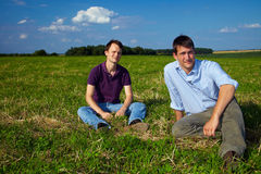 Two men sitting in a field Stock Image